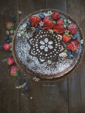 Top view of a gingerbread cake decorated with powdered sugar and berries