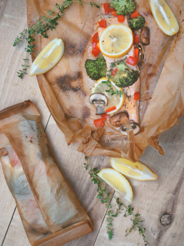 Top view of salmon cooked in parchment paper with vegetables