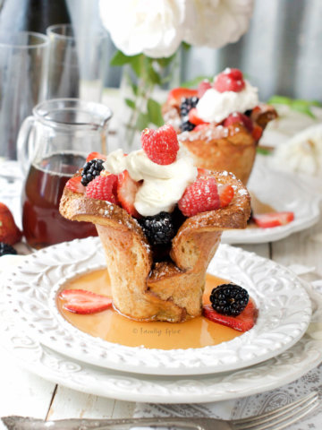 Side view of baked french toast cups filled with berries and whipped cream