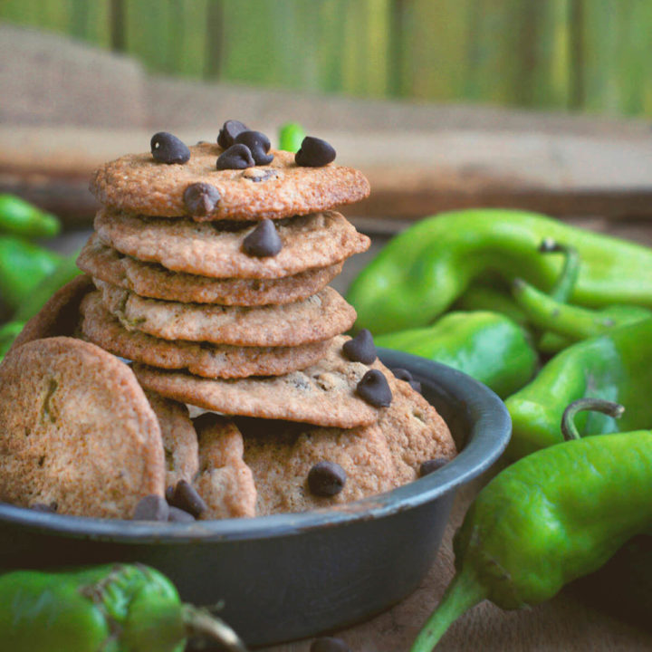 A stack of chocolate chip cookies made with and surrounded by green Hatch chiles