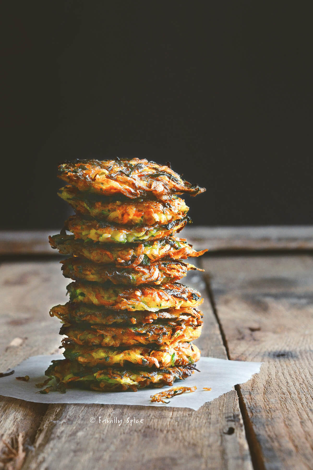 A stack of vegetable latkes on a dark and rustic background