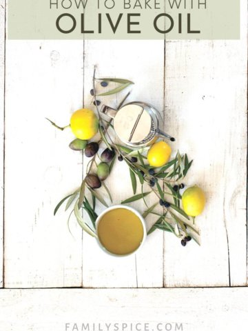 Some olive tree branches with olives, lemons and olive oil on a white background