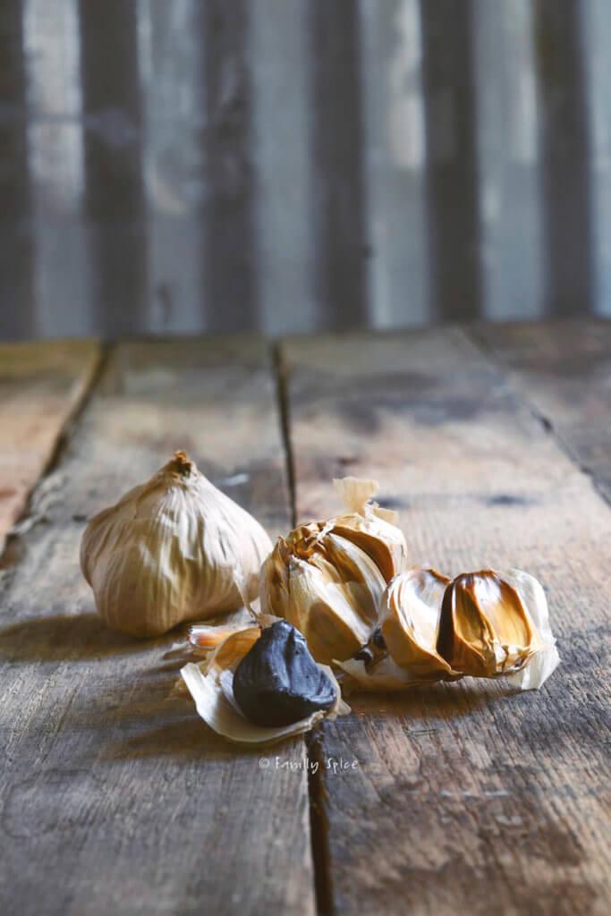Fermented black garlic on a rustic background
