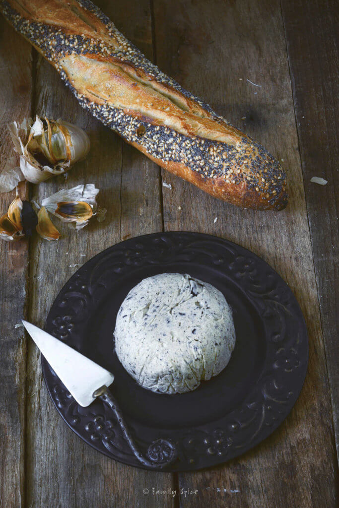 Black garlic butter compound on a black plate with a small knife and a seeded baguette next to it