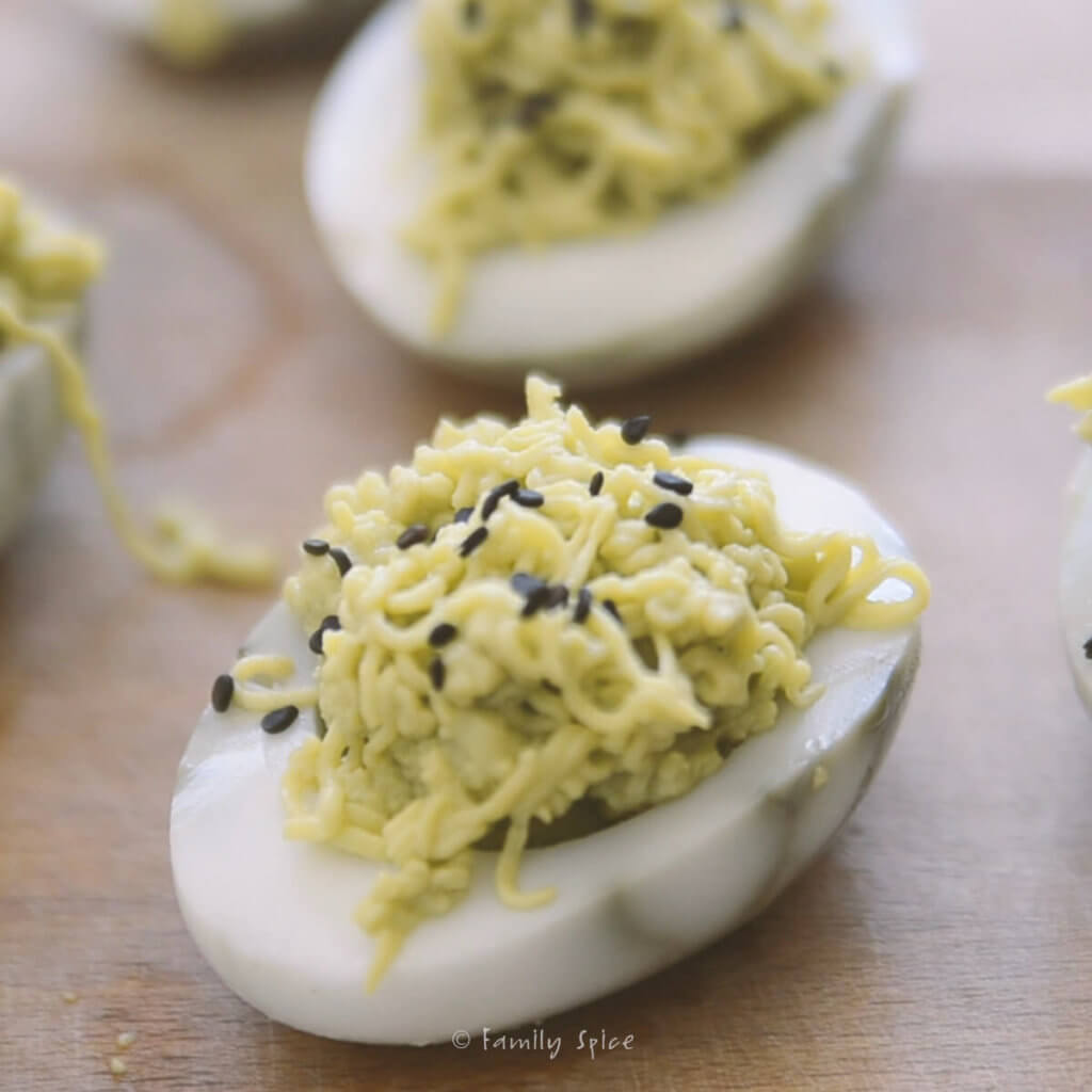 Garnishing green halloween deviled eggs with black sesame seeds