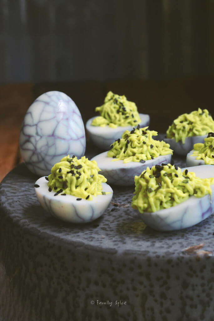 Halloween deviled eggs made with green filling and web design on the whites