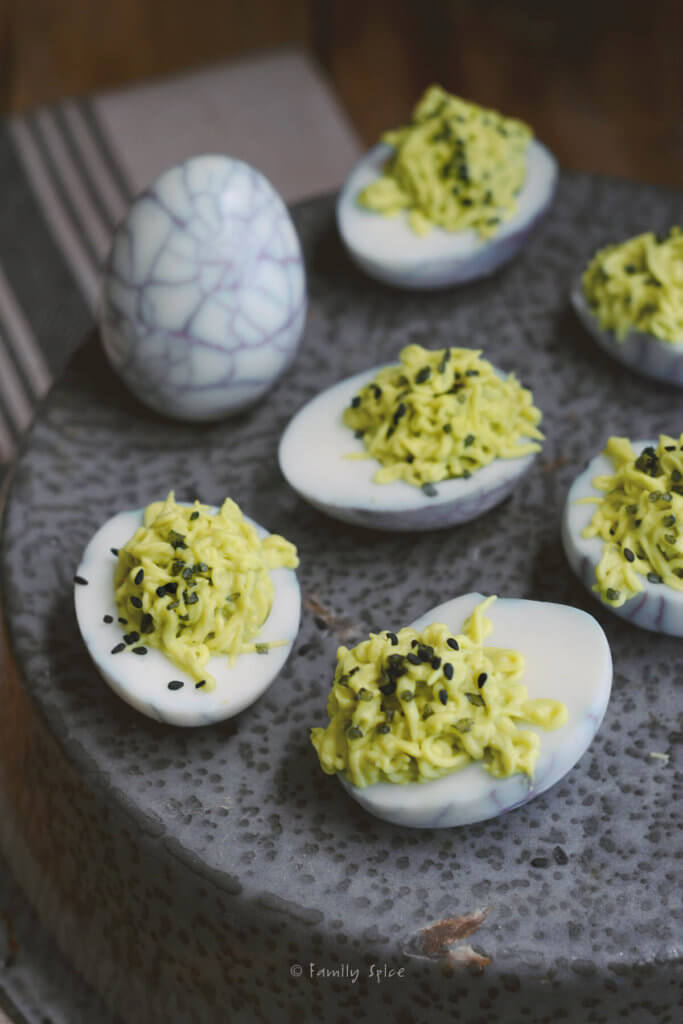 Closeup of halloween deviled eggs made with green filling and web design on the whites