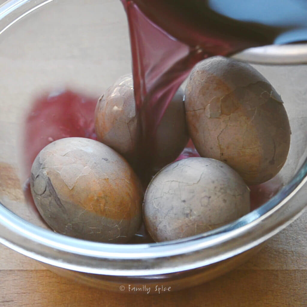 Adding blueberry water into a bowl with cracked hard boiled eggs