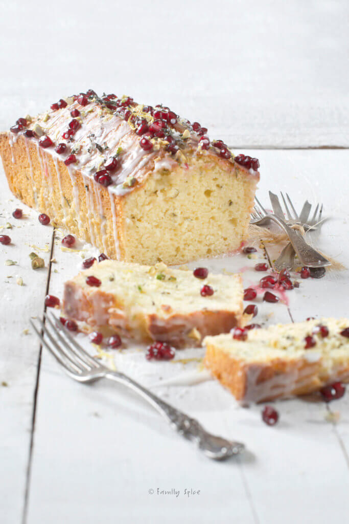 An olive oil lemon cake baked in a loaf pan and garnished with pistachios and pomegranate arils