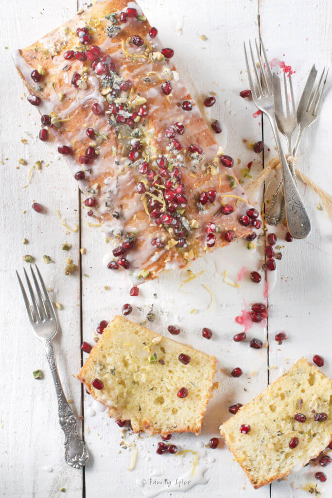Top view of a olive oil lemon cake baked in a loaf pan and garnished with pistachios and pomegranate arils with slices next to it