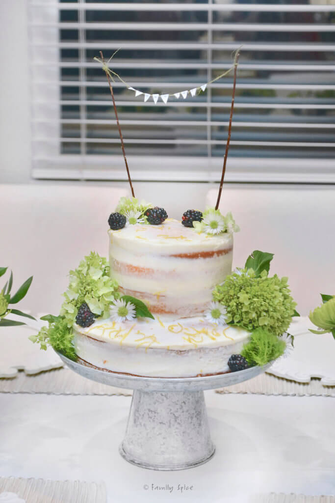 A 3 layer naked lemon cake garnished with flowers and berries