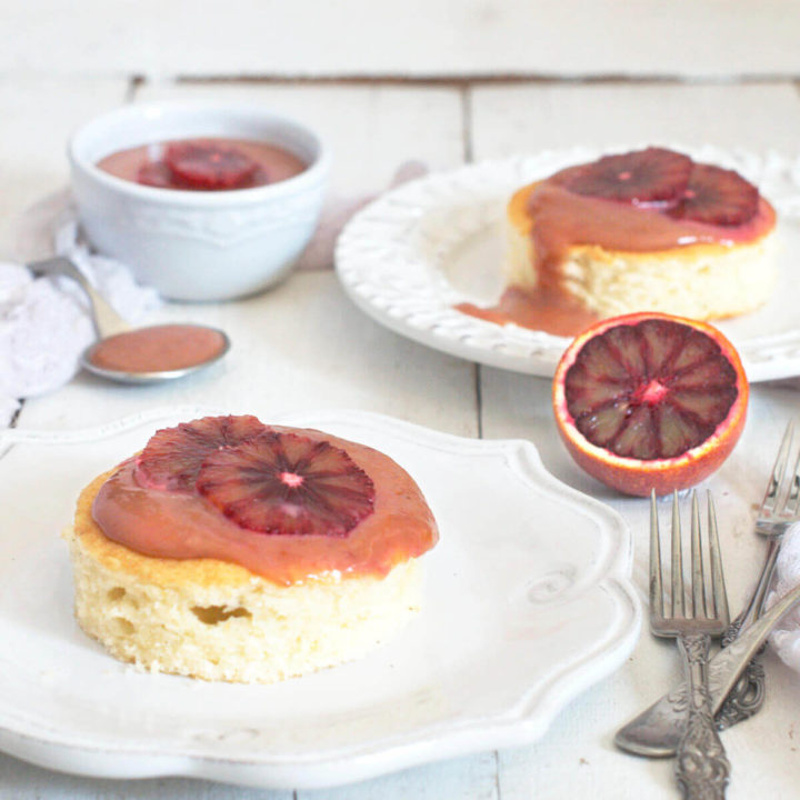 Side view of two plates with small cakes topped with blood orange curd with a bowl of blood orange curd next to it