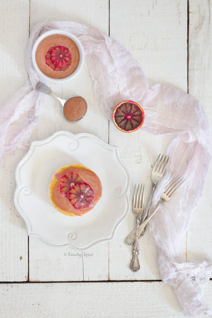 Top view of a small cakelet on a white plate topped with blood orange curd with a bowl of blood orange curd next to it