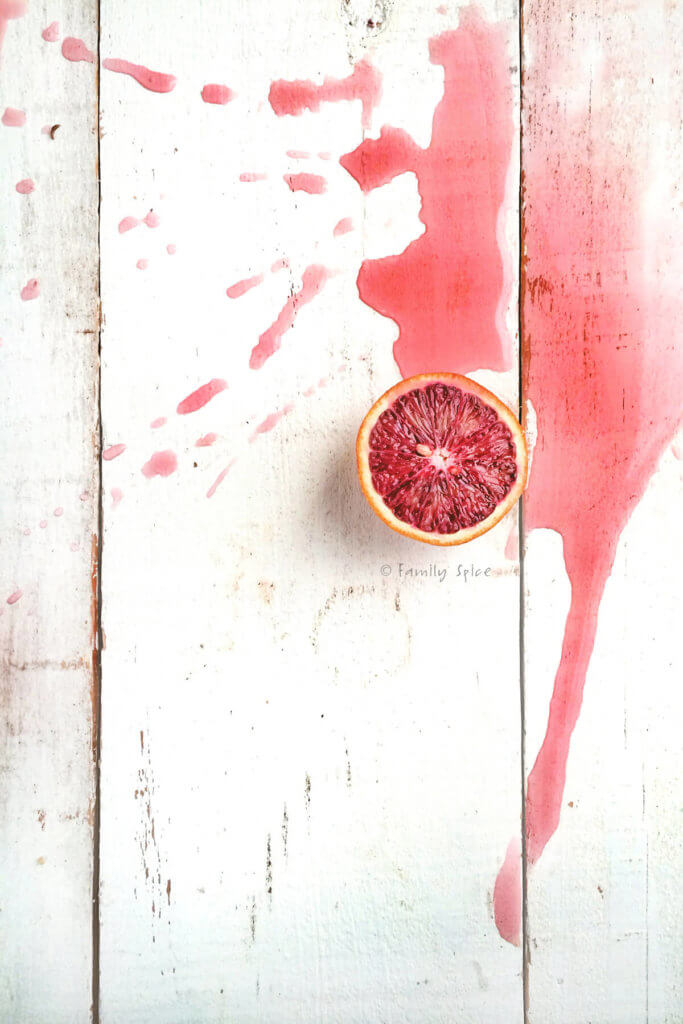A halved blood orange with blood orange juice spilled next to it on a white surface