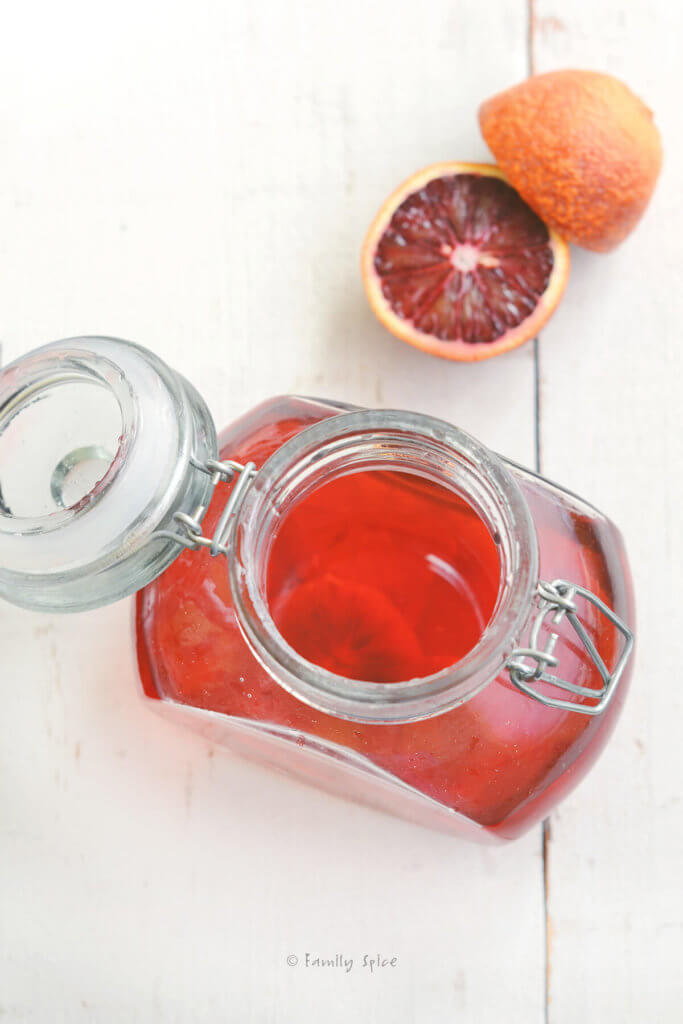 Top view of a glass jar with blood orange flavored vinegar in it with a blood orange next to it