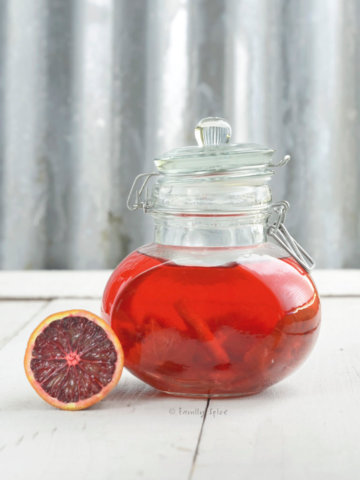Blood oranges infusing vinegar in a glass jar with a blood orange next to it