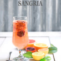 A tall footed glass with pink citrus sangria and citrus fruits around it by FamilySpice.com