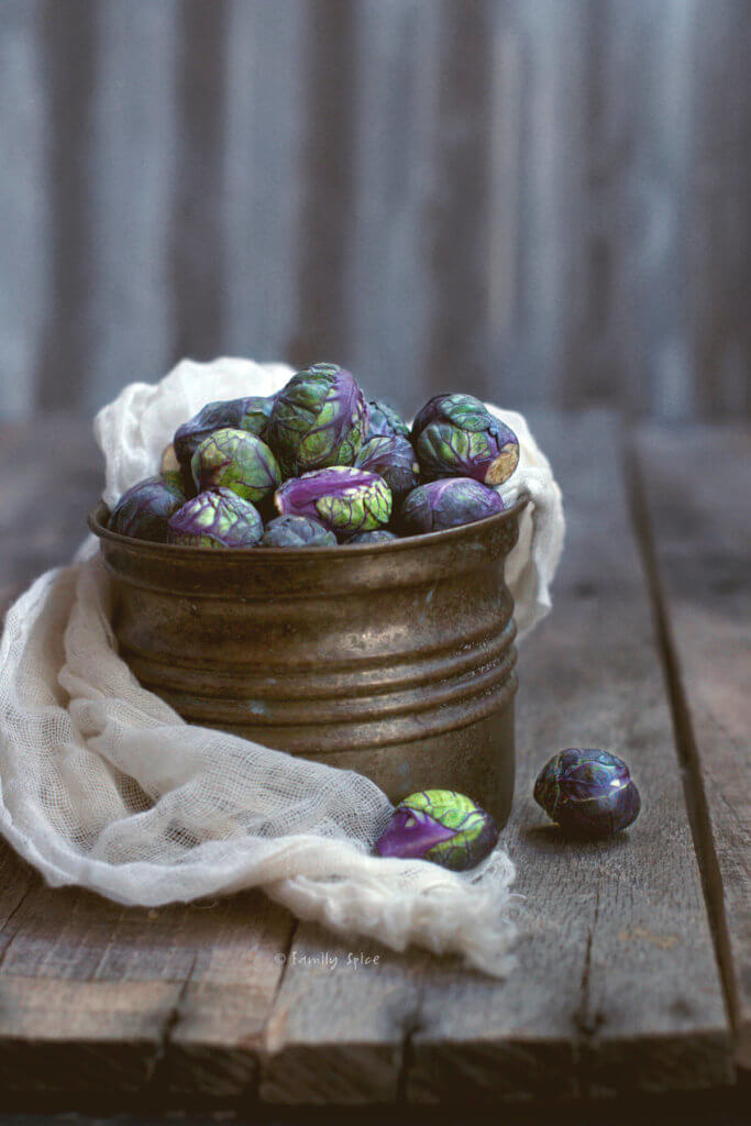 A tin of purple Brussels sprouts on a dark and rustic background
