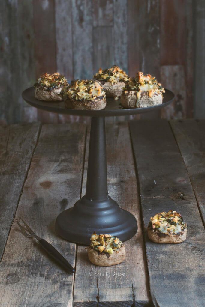 Several quinoa and cheese stuffed mushrooms on a dark cake pedestal