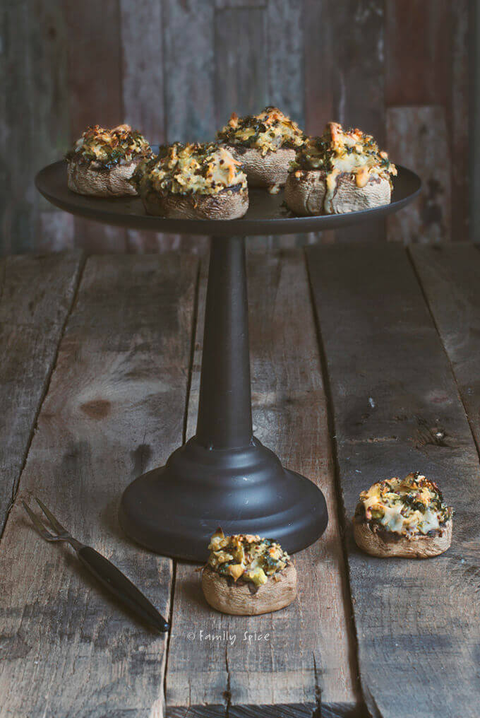 A metal stand full of quinoa and artichoke stuffed mushrooms by FamilySpice.com