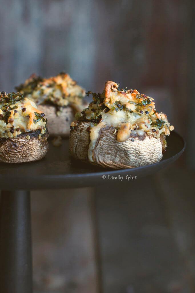 Closeup of quinoa and cheese stuffed mushrooms on a dark cake pedestal