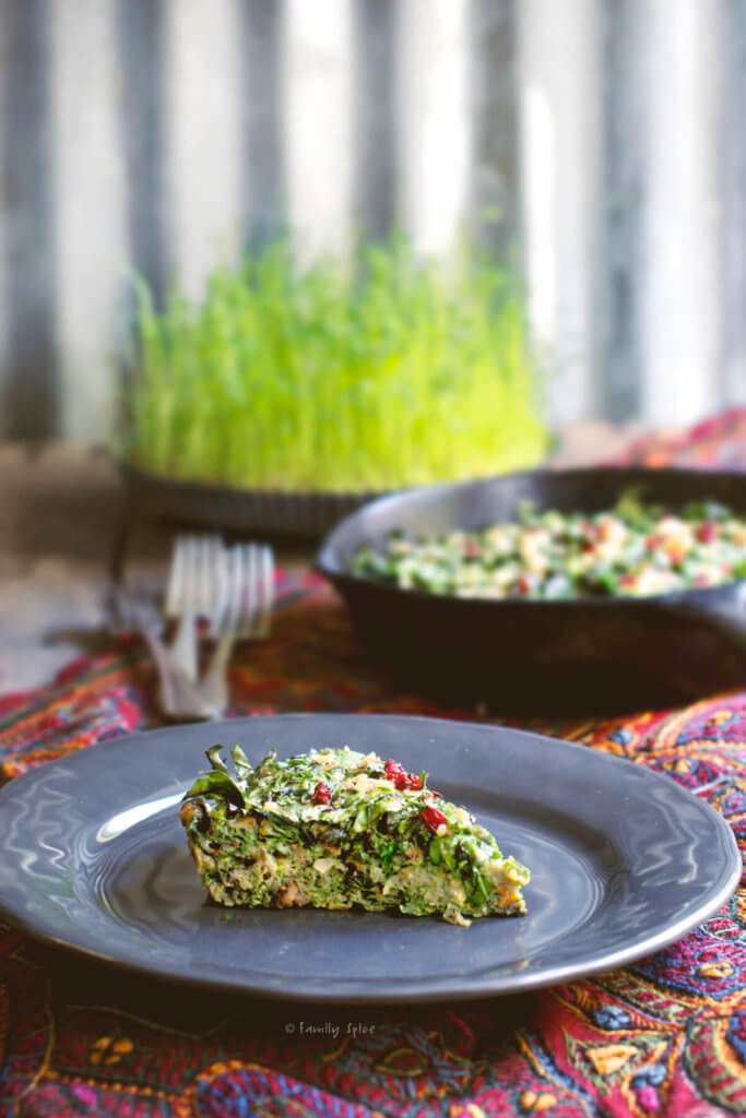 A slice of kuku sabzi (persian herb frittata) on a grey plate with a cast iron pan and a plate of sprouts behind it
