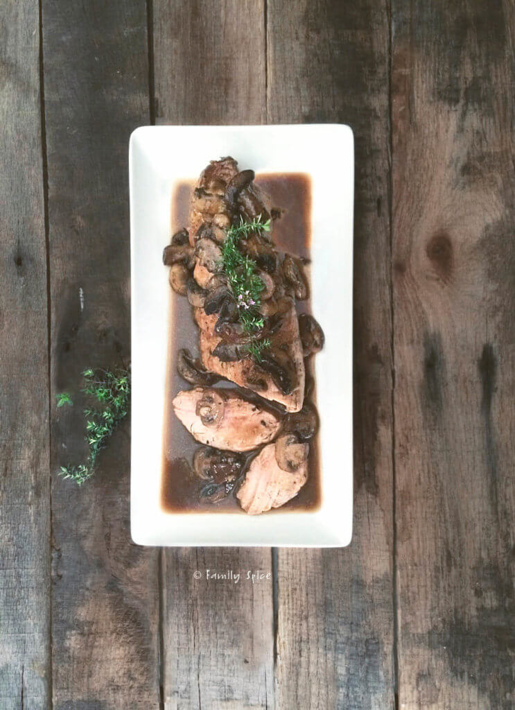 Top view of a pork tenderloin roasted with mushrooms and port sauce garnished with thyme