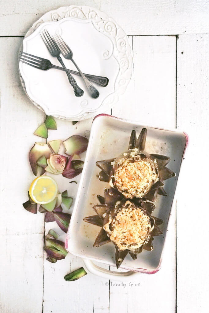 Top view of two Italian stuffed artichokes baked in white stoneware
