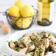 Braised baby artichokes with mushrooms and lemons with a basket of lemons and a bottle of white wine behind it