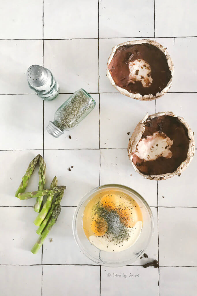 Hollowed out portobello mushroom caps with asparagus spears, egg mixture and salt and pepper shakers
