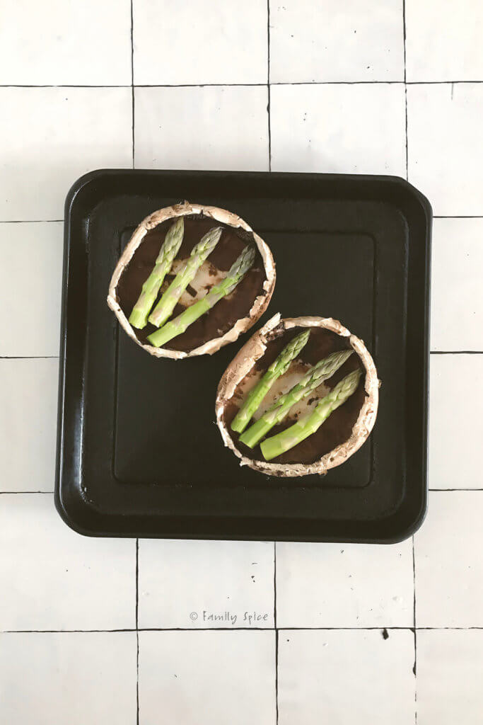 Top view of two portobello mushrooms with asparagus on a baking sheet