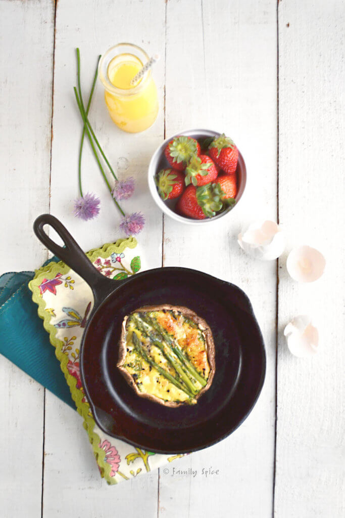 Overhead view of a portobello keto quiche in a cast iron pan with a carafe of orange juice and bowl of strawberries next it