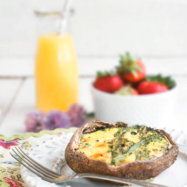 Side view of a portobello keto quiche in a cast iron pan with a carafe of orange juice and bowl of strawberries behind it