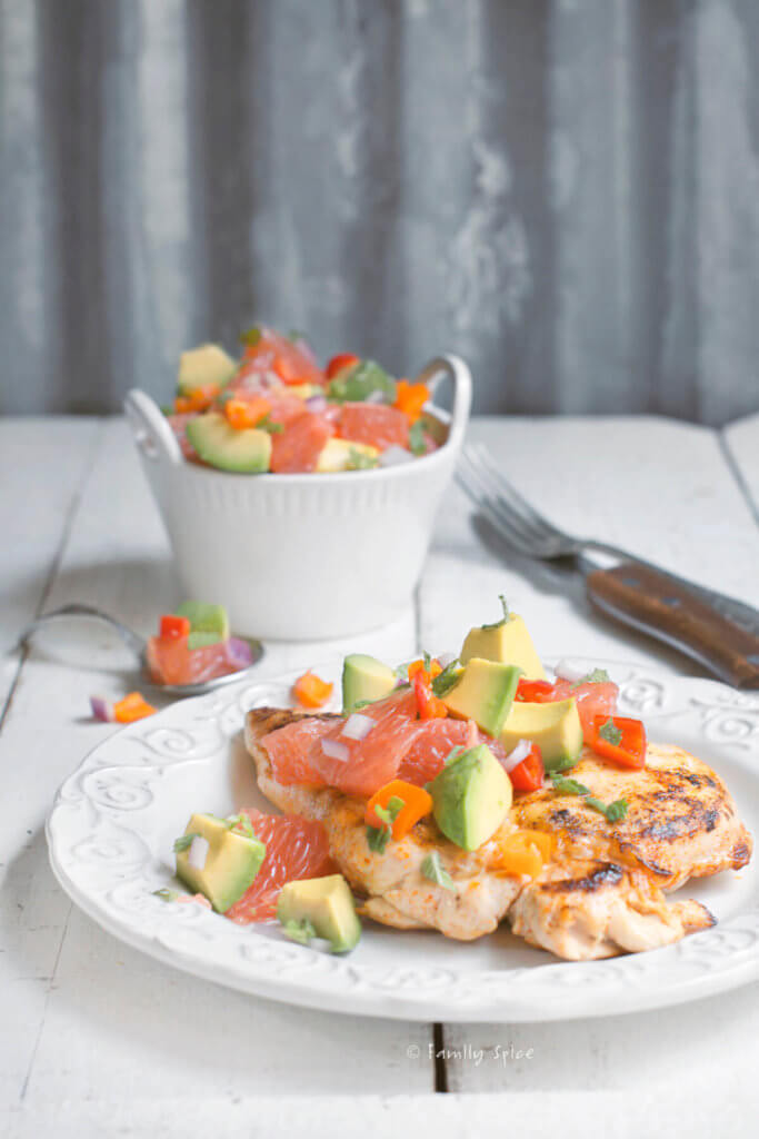 A white plate with chicken breast topped with avocado grapefruit salad with a small bowl of salad behind it