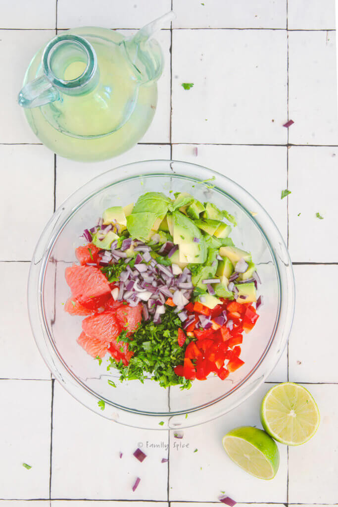 A clear bowl with grapefruit segments, avocado chunks, chopped bell pepper, cilantro and red onions