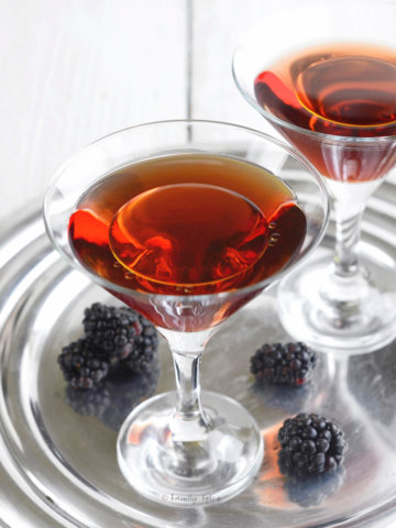 Closeup of two martini glasses with a blackberry cocktail in it and topped with a splash of olive oil