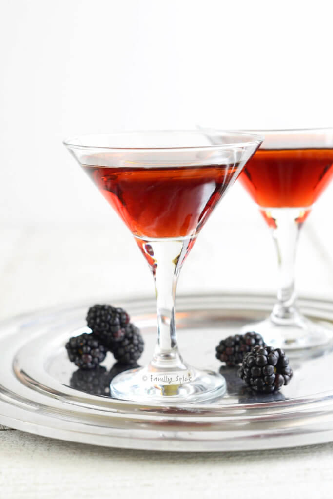 Side view of two martini glasses with a blackberry cocktail in it and topped with a splash of olive oil