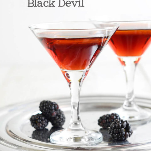 Side view of two martini glasses filled with Blackberry Black Devil cocktail with an olive oil floater by FamilySpice.com