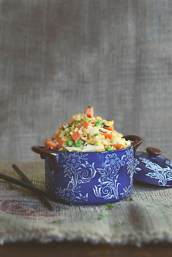 Sideview of a small blue ceramic pot filled with fried brown rice with carrots, corn, peas and sausage by FamilySpice.com