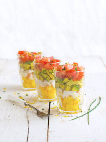 Layers of chopped peach, crab, avocado and tomatoes in small shot glasses