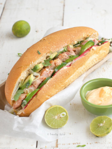 closeup of a chicken banh mi sandwich stuffed with jalapeños, avocado, radishes and sriracha mayonnaise