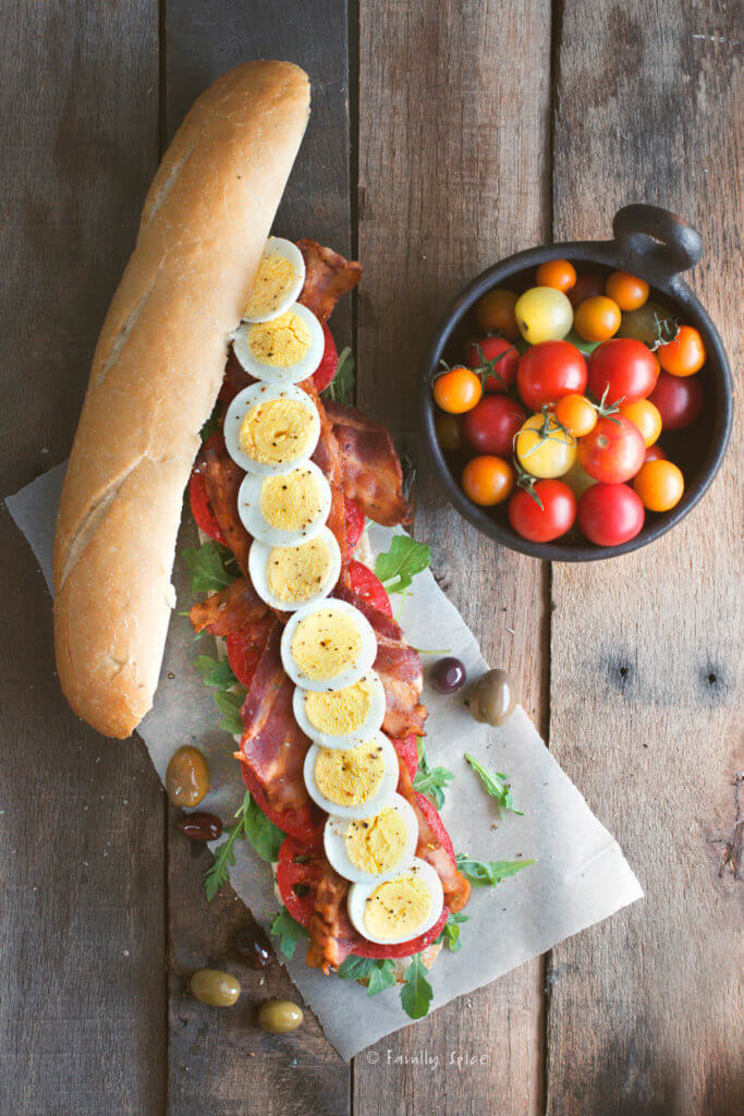 Top view of a baguette filled with slices of hard boiled egg, tomatoes, lettuce and bacon