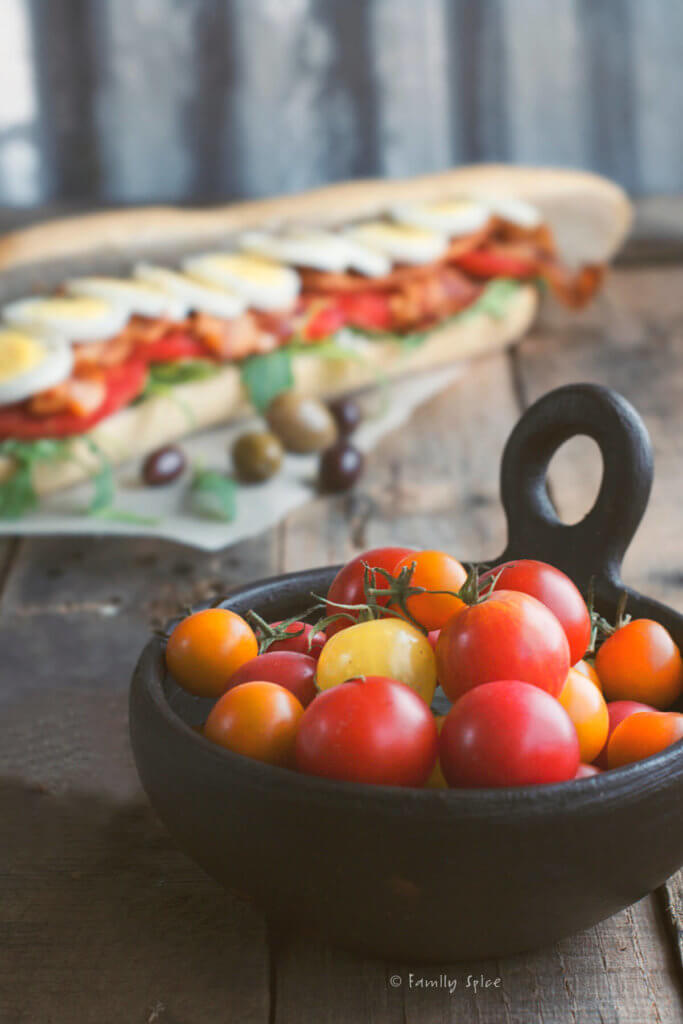 Closeup of a bowl of cherry tomatoes with a long baguette filled with hard boiled eggs, tomatoes, lettuce and bacon