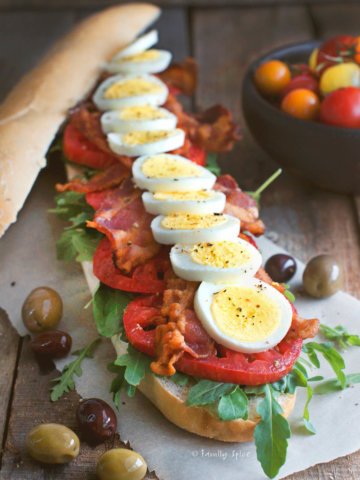 Side view of a baguette filled with slices of hard boiled egg, tomatoes, lettuce and bacon