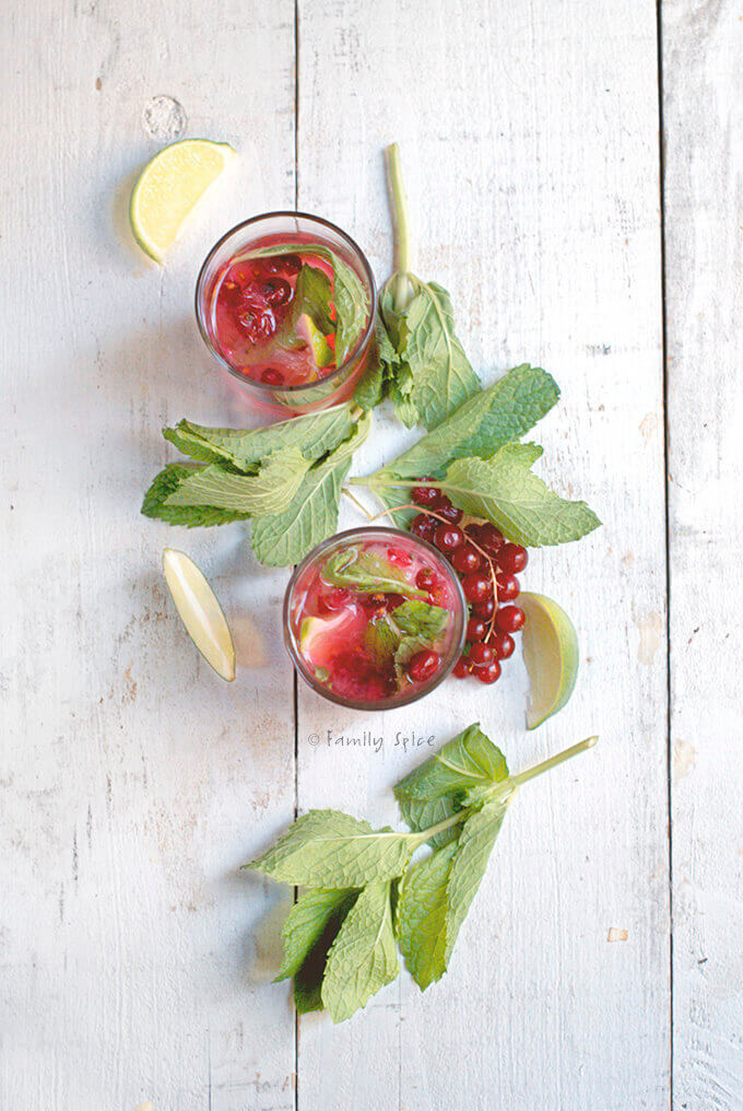 Top view of two glasses filled with red currant mojito surrounded by fresh mint and lime wedges by FamilySpice.com