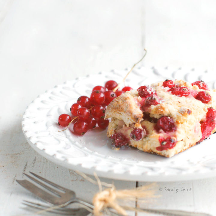 Red currant scone on a white plate with small fork next to it