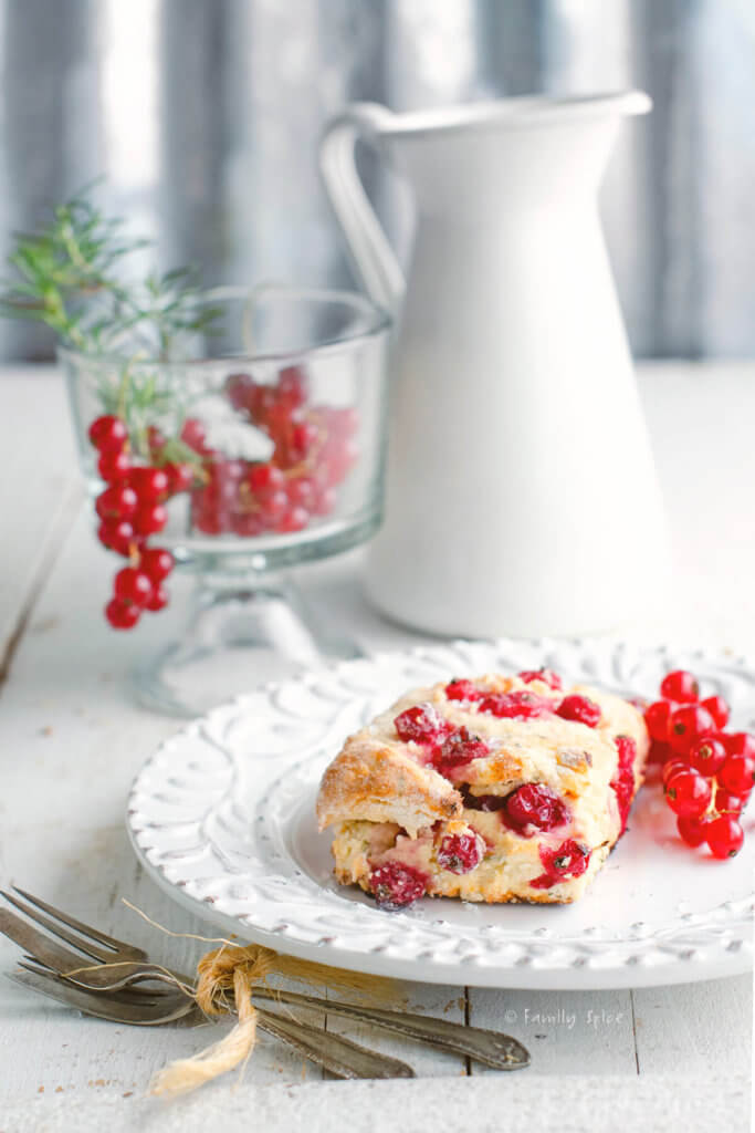 Closeup of a red currant scone on a white plate with red currants and a white enamel pitcher behind it