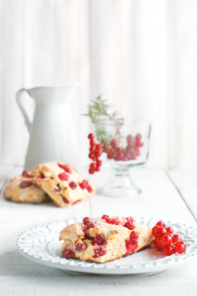 A red currant scone on a white plate with red currants and a white enamel pitcher behind it