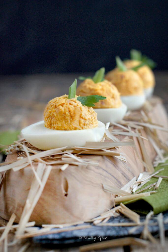 Pumpkin and ham stuffed deviled eggs on a wooden platter