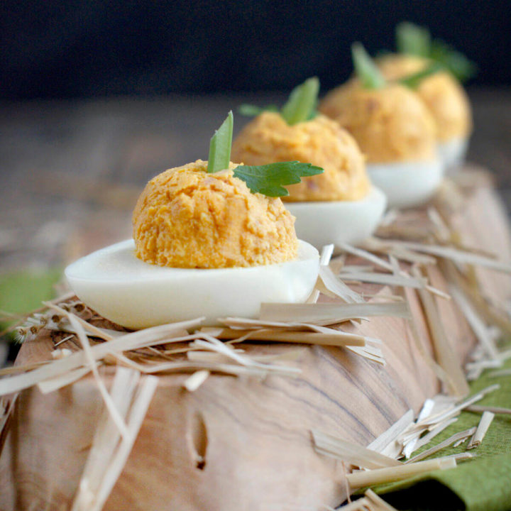 Pumpkin and ham stuffed deviled eggs on a wooden platter
